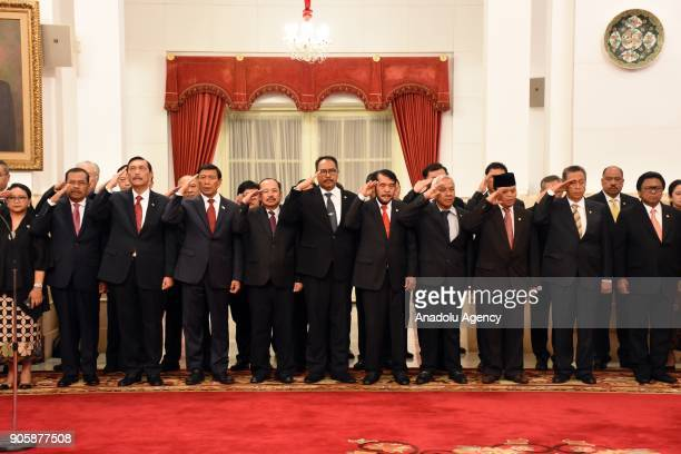 Members of Indonesian cabinets salute during national anthem within an inauguration ceremony at the State Palace in Jakarta Indonesia on January 17...