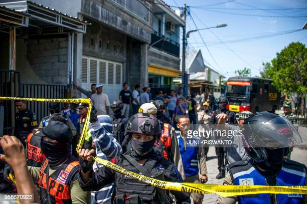 Members of Indonesia's Densus 88 counterterror police squad cordon an area as they conduct a raid on the residence where a family suspected of taking...