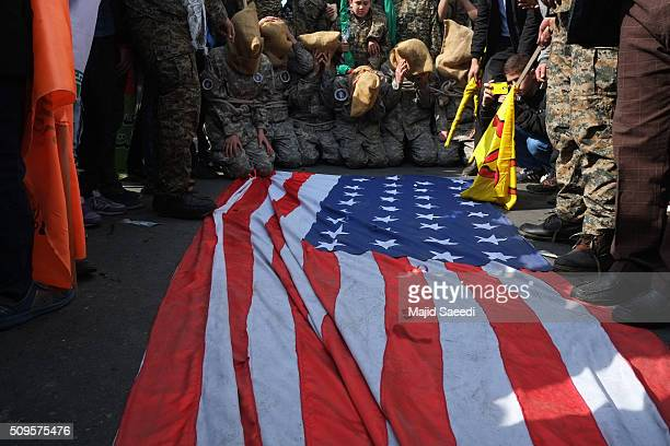 Members of Iranian Basij paramilitary force reenact the January capture of U.S sailors by the Revolutionary Guard in the Persian Gulf at a rally to...