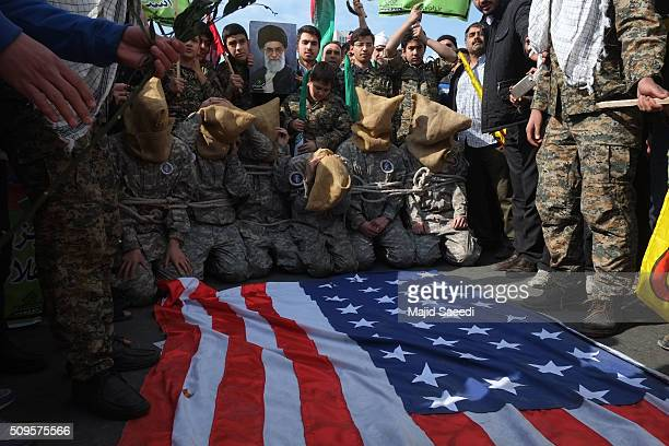 Members of Iranian Basij paramilitary force reenact the January capture of US sailors by the Revolutionary Guard in the Persian Gulf at a rally to...