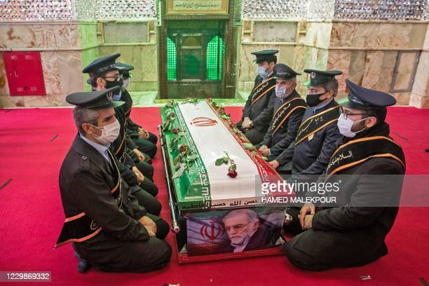 Members of Iranian forces pray around the coffin of slain nuclear scientist Mohsen Fakhrizadeh during the burial ceremony at Imamzadeh Saleh shrine...
