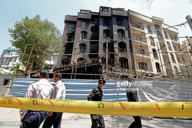 Members of Iranian security forces walk by at the cordoned-off site of an explosion at the Sina At'har health centre in the upmarket northern...