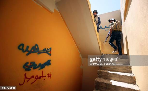 Members of Iraqi forces ascend stairs in a house on the front line in the old city of Mosul on May 24 during the ongoing offensive to retake the area...
