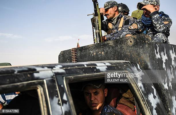 Members of Iraqi forces drive their armoured vehicle as they head to the frontline on October 18 2016 near the town of Qayyarah south of Mosul during...