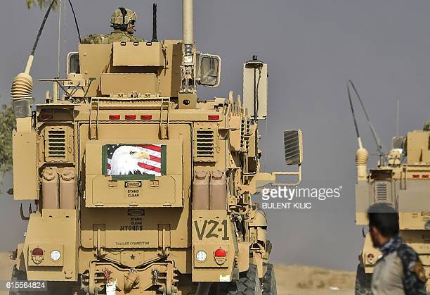 Members of Iraqi forces look at a MRAP armoured vehicle used by US forces supporting Iraq troops during the operation to recapture Mosul from the...