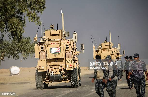Members of Iraqi forces walk near a MRAP armoured vehicle used by US forces supporting Iraq troops during the operation to recapture Mosul from the...