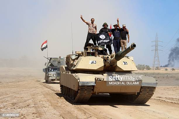 Members of Iraqi government forces celebrate on a tank with a seized flag of the Islamic State group after they retook an area from its jihadists on...