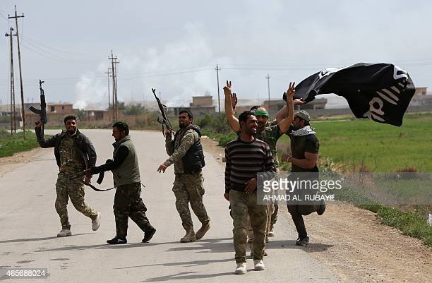 Members of Iraqi paramilitary Popular Mobilisation units which are dominated by Shiite militias celebrate with a flag of the Islamic State group...