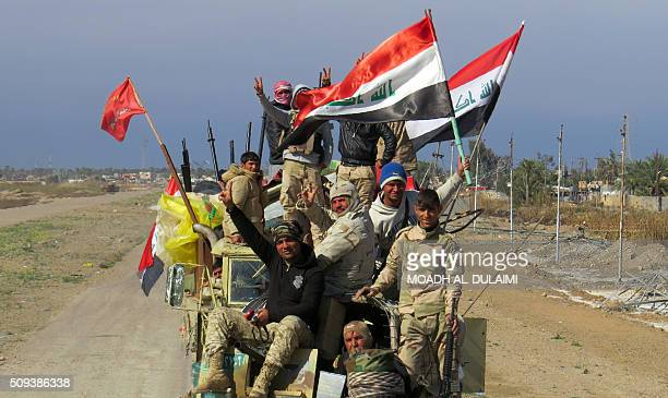 Members of Iraqi progovernement forces flash the sign of victory and hold national flags atop their vehicle in the Saida area in the southern...