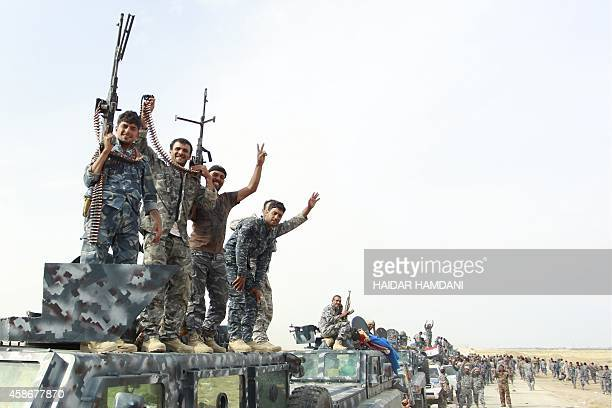 Members of Iraqi progovernment forces celebrate as they stand on vehicles positioned on a road near the town of Jurf alSakhr located between Baghdad...