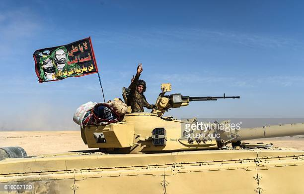 Members of Iraqi progovernment forces drive a tank with a flag bearing a portrait of Prophet Mohammed's grandson Imam Hussein on it on October 21 as...