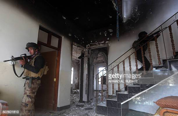 Members of Iraq's elite counterterrorism search a heavily damaged building on December 27 2015 in the Hoz neighbourhood in central Ramadi the capital...