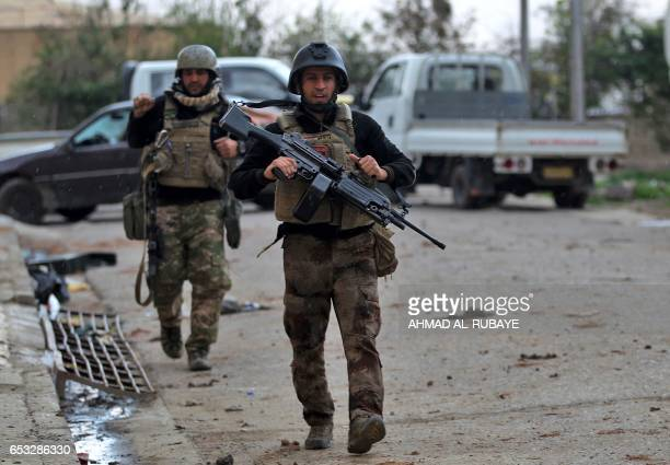 Members of Iraq's elite CounterTerrorism Service advance towards Mosul's alNasser neighbourhood on March 14 2017 during the ongoing offensive to...