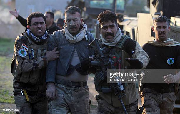 Members of Iraq's elite counterterrorism service help a comrade who was wounded in fighting with the Islamic State group's jihadists in the...
