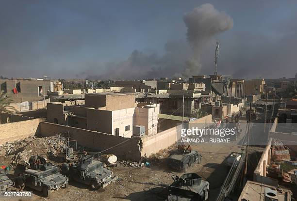 Members of Iraq's elite counterterrorism service patrol as smoke billows in the background following a reported air strike by the USled coalition on...