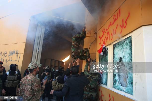 TOPSHOT Members of Iraq's Hashed alShaabi military network attempt to break into the US embassy in the capital Baghdad on December 31 during a rally...