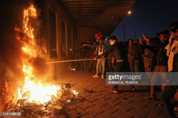 Members of Iraq's Hashed alShaabi military network set a door ablaze as they try to break into the US embassy building in the capital Baghdad on...