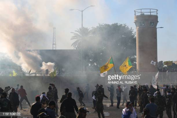 Members of Iraq's Hashed alShaabi military network try to breach the outer wall of the US diplomatic mission in the capital Baghdad on December 31...