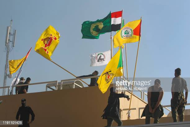 Members of Iraq's pro-Iranian Hashed al-Shaabi group poise flags of the group and its factions on the rooftop of the US embassy building in the...