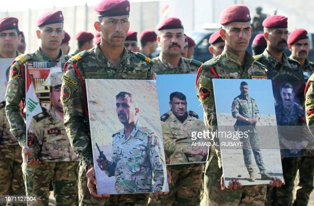 Members of Iraq's Rapid Response military unit hold portraits of fallen soldiers during the fight against Islamic State group jihadists during a...