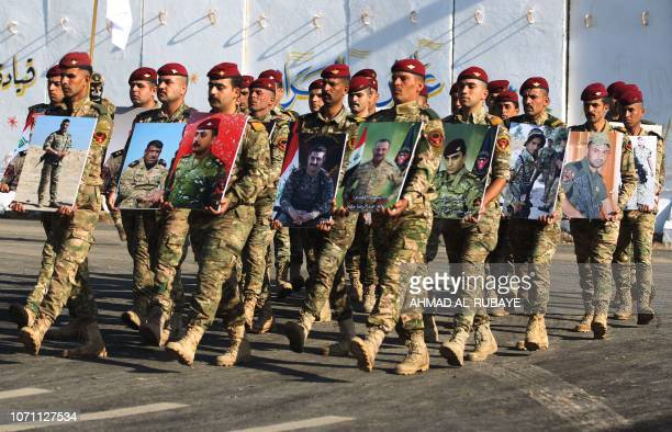 TOPSHOT Members of Iraq's Rapid Response military unit hold portraits of fallen soldiers during the fight against Islamic State group jihadists...