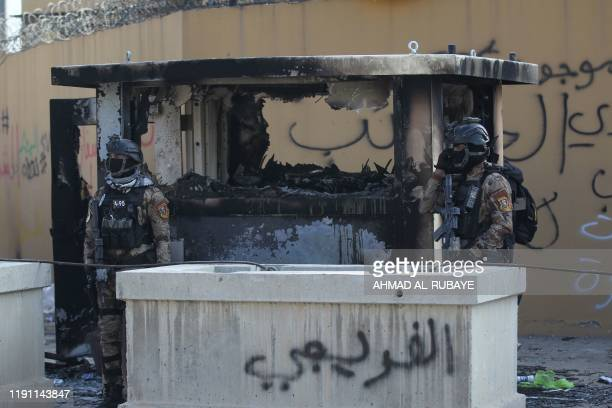 Members of Iraq's security forces stand guard in front of the US embassy in the capital Baghdad after an order from the Hashed alShaabi paramilitary...