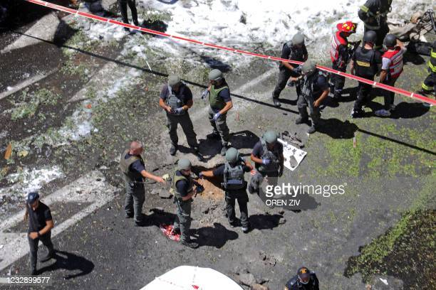 Members of Israeli security and emergency services inspect the damages in Ramat Gan near the coastal city of Tel Aviv, on May 15 following the...