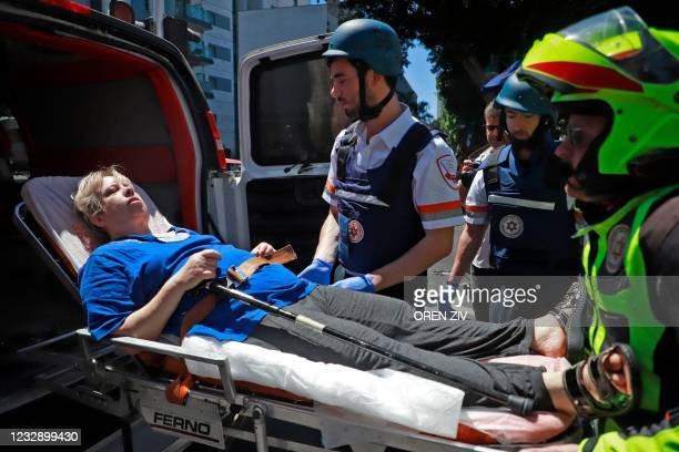 Members of Israeli security and emergency services transport an injured woman from a site hit by a rocket in Ramat Gan near the coastal city of Tel...