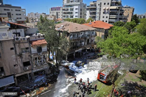 Members of Israeli security and emergency services work on a site hit by a rocket in Ramat Gan near the coastal city of Tel Aviv, on May 15 following...