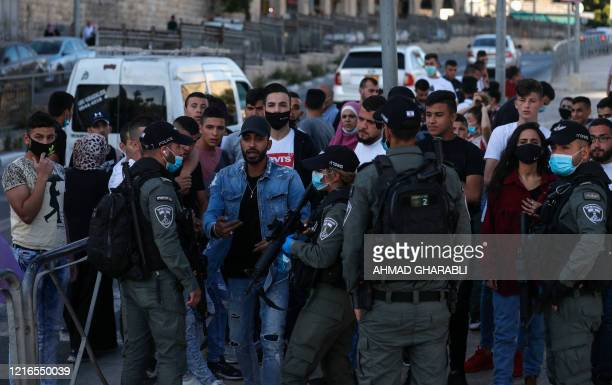 Members of Israeli security forces block the way as Palestinian protesters demonstrate at the Damascus Gate of the old city of Jerusalem on May 31 to...