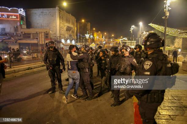 Members of Israeli security forces detain a Palestinian man amid clashes with Palestinian protesters outside Damascus Gate in Jerusalem's Old City on...