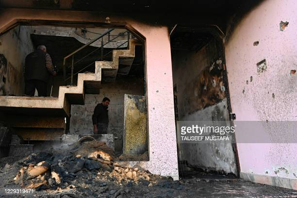 Members of Jammu and Kashmir police bomb squad inspect a damaged house after a gunbattle between suspected militants and government security forces...