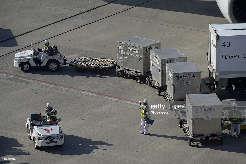Members of Japan Airlines Co.'s (JAL) ground staff unload cargo containers from an aircraft at Haneda Airport in Tokyo, Japan, on Sunday, Feb. 3, 2013. Japan Airlines, the nation's largest carrier by market value, is scheduled to release earnings on Feb. 4. Photographer: Akio Kon/Bloomberg via Getty Images