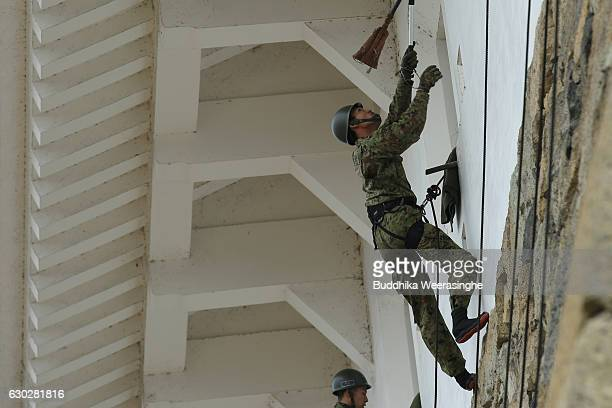 Members of Japan Ground SelfDefense Force climb the stone wall of the main castle building to clean and remove weeds during the annual cleaning day...