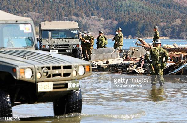 Members of Japan Ground SelfDefense Force stand in the flooded area to look for victims' bodies on April 1 2011 in Ishinomaki Miyagi Japan More than...