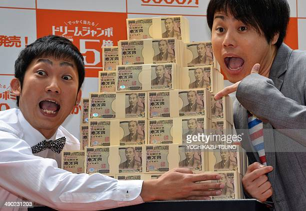 """Members of Japanese comic group Non style, Akira Ishida and Yusuke Inoue pose with 550 million yen in cash for the """"Dream Jumbo Lottery"""" as the first..."""