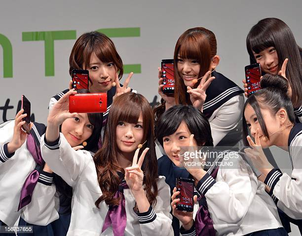 Members of Japanese pop group 'Nogizaka 46' take their self portraits as they display Taiwan's electronics giant HTC's new smartphone 'HTCJ...