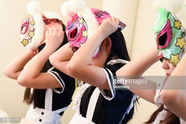 Members of Japanese pop group 'Virtual Currency Girls' adjust their masks ahead of performing onstage in Tokyo Japan on Friday Feb 16 2018 The...