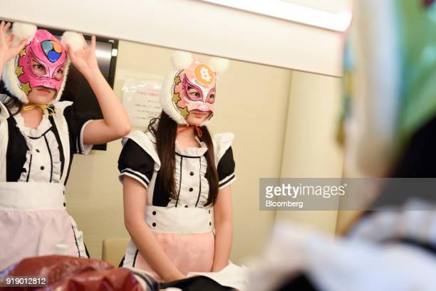 Members of Japanese pop group 'Virtual Currency Girls' check their outfits in a mirror ahead of performing onstage in Tokyo Japan on Friday Feb 16...