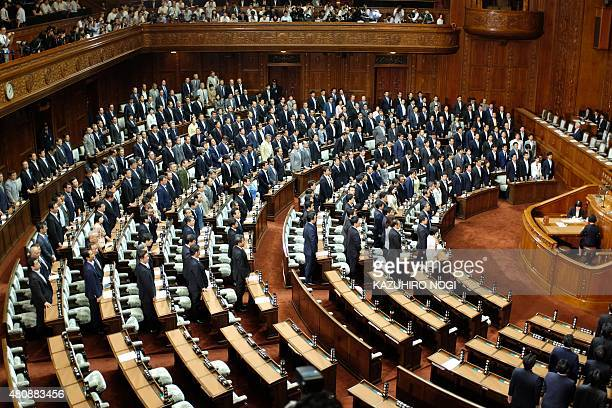 Members of Japanese Prime Minister Shinzo Abe's Liberal Democratic Party and its coalition partner the Komeito party stand as controversial security...