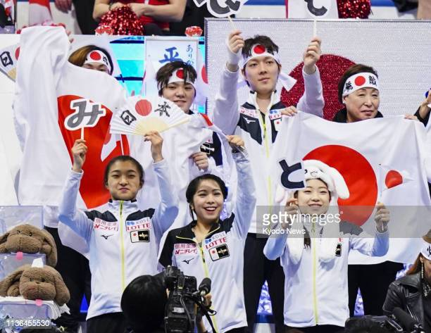 Members of Japan's figure skating team cheer for ice dancers Misato Komatsubara and Tim Koleto at the end of their free dance at the World Team...