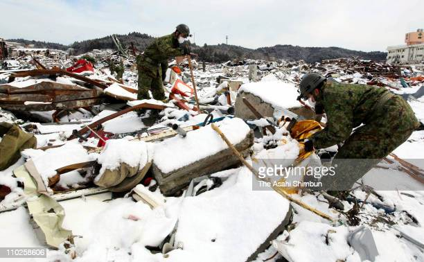 Members of Japan's Ground SelfDefense Force continue the rescue work in snowcovered debris on March 17 2011 in Minamisanriku Miyagi Japan The quake...