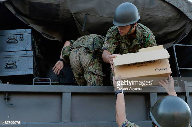 Members of Japan's self defence force hand our relief goods on September 11 2015 in Joso Japan Search and rescue operations were underway after two...