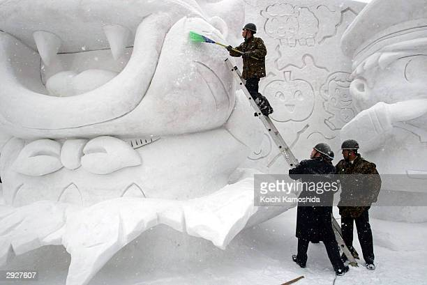 Members of Japan's Self Defence Force prepare a snow sculpture prior to Sapporo Snow Festival February 4 2004 in Sapporo Japan The festival marks its...