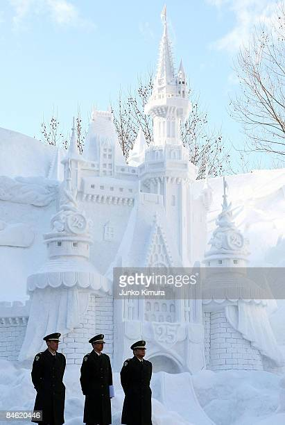 Members of Japan's Self Defence Force stand in front of a snow castle ahead of the opening of the 60th Sapporo Snow Festival at Odori Park on...