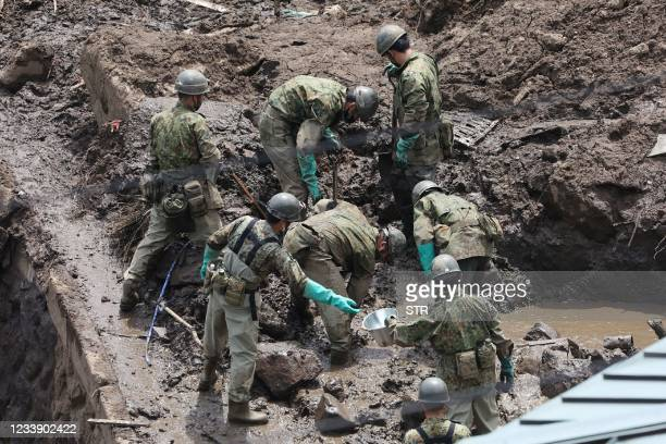 Members of Japan's Self-Defence Forces search for missing people at the scene of a landslide following days of heavy rain in Atami, Shizuoka...