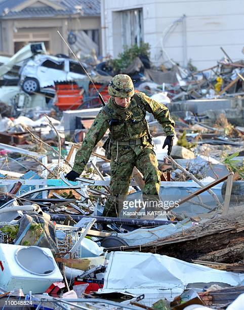 A members of Japan's SelfDefense Force work in the debris caused by Friday's 90 magnitude earthquake and ensuing tsunami on March 14 2011 in Miyagi...