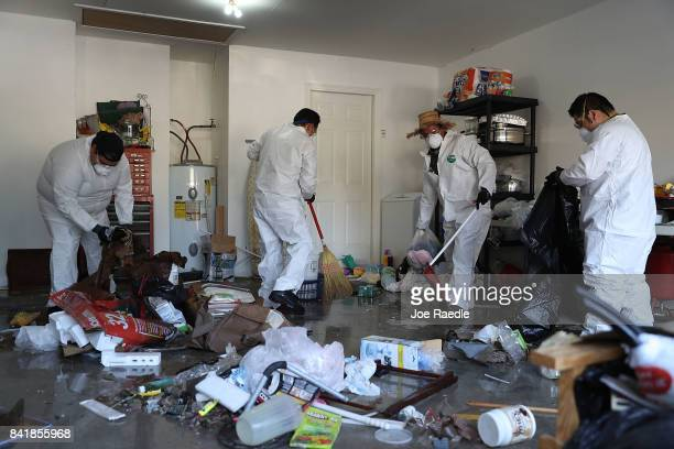 Members of Jehovah's Witnesses help a friend clean up their home after flood water inundated it as the family begins the process of rebuilding after...