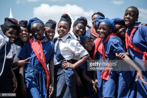 TOPSHOT Members of Kenya Girl Guides take photos after attending ceremony of the International Women's day at Kawangware in Nairobi Kenya on March 8...