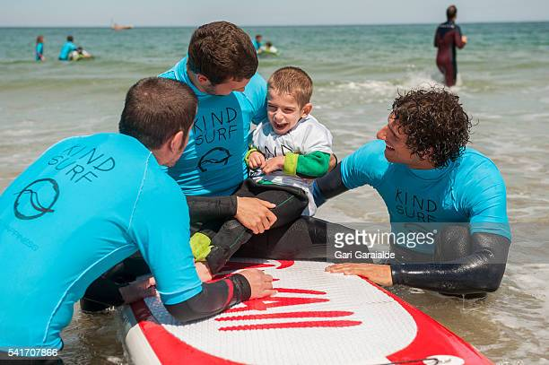 Members of Kind Surf NGO help some kids to surf on the International Surf Day on June 20 2016 in San Sebastian Spain Kind Surf NGO is dedicated to...